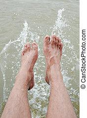 Foot of man in the water splashing