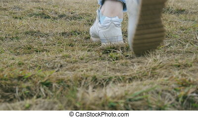 Foot of woman stepping up to the hill. Female legs in sneakers walking over green grass at the park. Low angle of view Close up