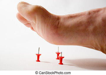 Foot stepping on tacks