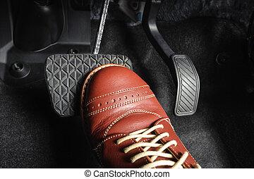 brake pedal - foot pressing the brake pedal of a car