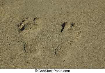Foot prints on the sand by the ocean