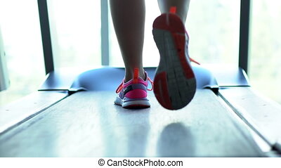 foot runner on a treadmill, close-up - foot of a female...