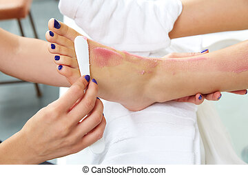 foot scrub pedicure woman leg in nail salon