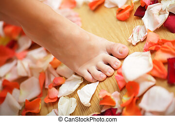 Foot stepping on the rose petals