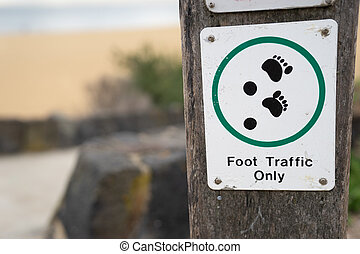 Foot Traffic only sign and symbol on wooden pole in beach path way walk area