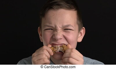 Footage boy eats chicken wings or nuggets, fast food -...