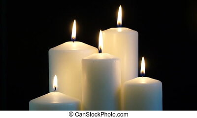 footage burning candles isolated on a black background.
