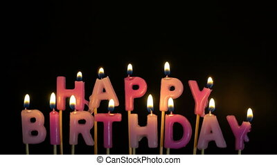 Footage colorful burning candles set on black background. Happy Birthday candles.
