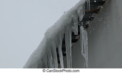 Footage Large icicles fall from the roof of the house. full...