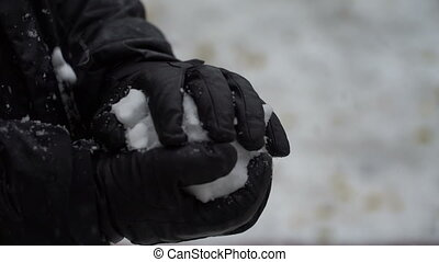 footage man sculpts hands a snowball outdoors.