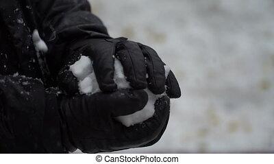footage man sculpts hands a snowball outdoors.