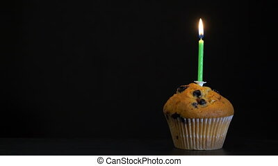 Footage muffin with a candle close up on black background. ...