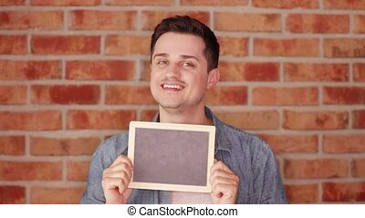 Footage of a young man holding a blackboard