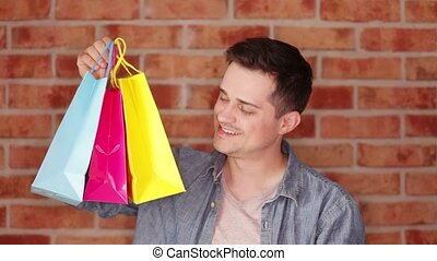 Footage of a young man holding a shopping bags