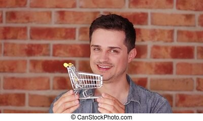 young man holding a shopping cart