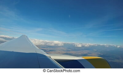 Footage of aerial view above clouds from airplane window with blue sky view from the airplane window to the blue sky and white clouds.