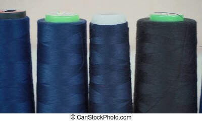 Video of multicolored spools of threads in workshop