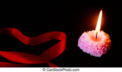 Footage of candle burning with ribbon for decoration Valentine day