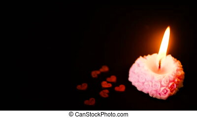 Footage of candle burning with wooden heart decoration. Valentine day