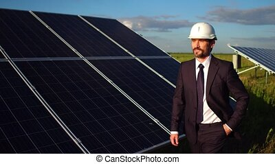 Footage of director checking installation of solar panels in the field.