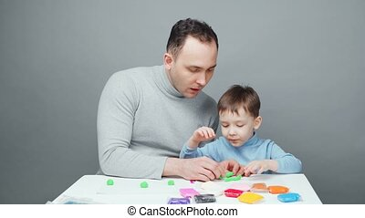 Footage of father and son sculpting in plasticine on gray ...
