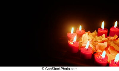 Footage of flower petals with candle burning for Valentine...