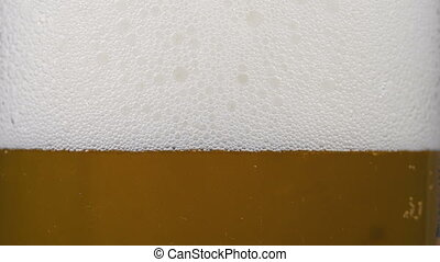 Footage of gold cold beer in glass with froth - Footage of...