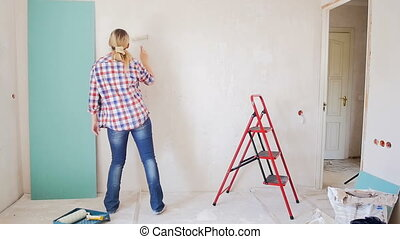 Footage of happy cheerful woman dancing while doing renovation at new apartment