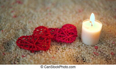 Footage of heart decoration and candle burning on sand. Valentine day