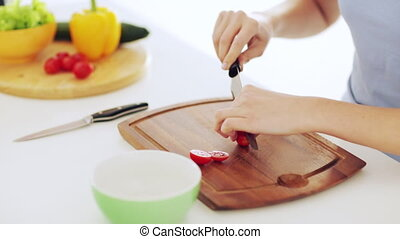 housewife cutting tomato in the kitchen - footage of...
