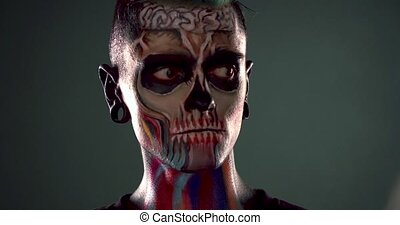 Footage of man with colored skull make up. Face art, male...