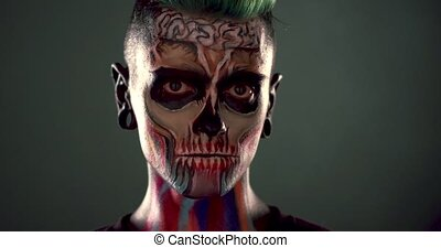 Footage of man with colored zombie makeup. Dead mask skull...