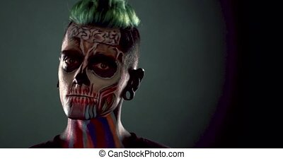 Footage of mans face with colored skeleton makeup. Face art,...