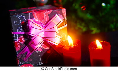 Footage of move gift boxes with candle burning and ornament...
