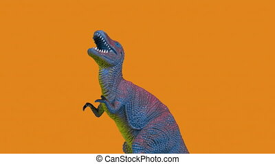 Animated stop motion footage of toy tyrannosaurus rex dinosaur moving towards the camera against changing colour background,