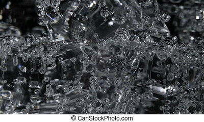 Footage of soda water with bubbles in glass on black...