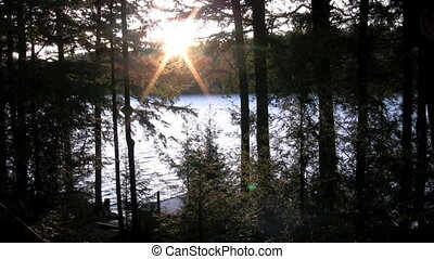 sunset - footage of sunset through trees over lake and dock