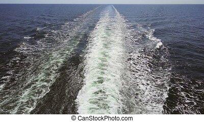 Footage of turquoise foamy sea waves behind rapid motor...
