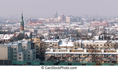 Panoramic footage of Wawel Royal Castle from Krakus Mound, the highest point in the city of Krakow, Poland. City skyline. Ancient buildings against the clear white sky in the background.