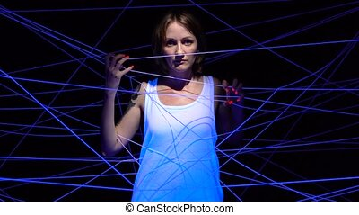Shooting of woman tangled in white threads in ultraviolet