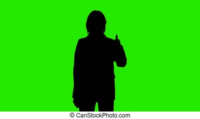 Footage of woman's silhouette in suit jacket with thumb gesture on green