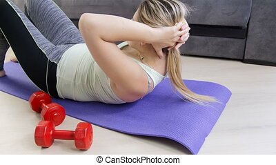 Footage of young sporty woman doing belly crunches on floor...