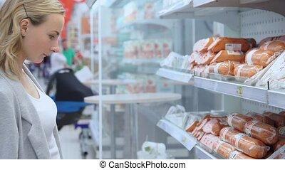 Footage woman buys sausage in supermarket. 4k video