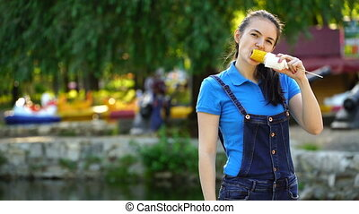 footage woman eating boiled corn in a park. 4k Video