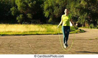 woman jumping on a skipping rope in a park. - footage woman...