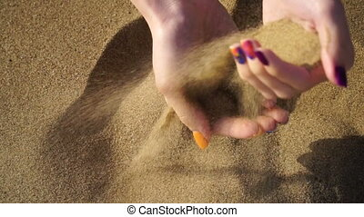 footage woman walking on the beach and holding a sand.