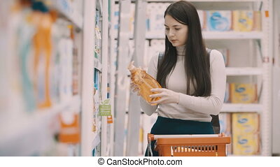 young women selecting detergents for house at supermarket -...