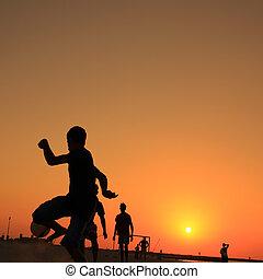 Football at Jumeira beach in Dubai during sunset.