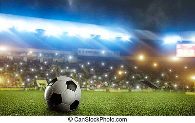 Football ball on green grass of the stadium field
