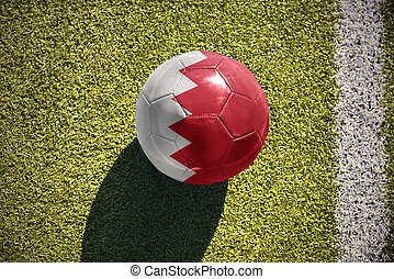 football ball with the national flag of bahrain lies on the field